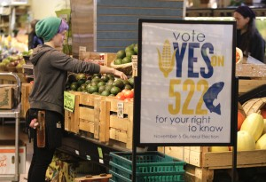 An employee stocks produce near a sign supporting a ballot initiative in Washington state that would require labeling of foods containing genetically modified crops at the Central Co-op in Seattle, Washington October 29, 2013. Major U.S. food and chemical companies are pouring millions of dollars into efforts to block approval of the initiative. REUTERS/Jason Redmond (UNITED STATES - Tags: BUSINESS POLITICS AGRICULTURE FOOD) - RTX14T89